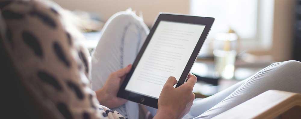 Woman reading an ebook on an tablet.